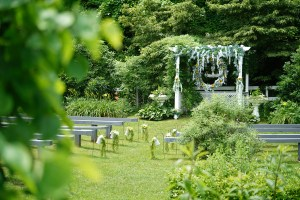 White wedding pergola with circular flower wreath and white flower vases in shepherd hooks down the aisle where couples get married at Honeysuckle Hills in the Smoky Mountains