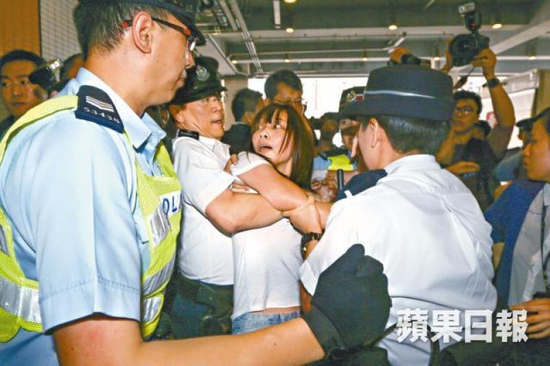 """A female HKFS official being """"bear hugged"""" by a male officer. File Photo: Apple Daily."""