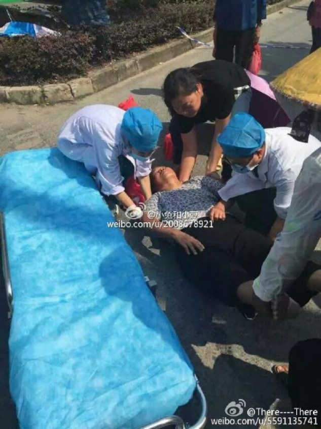 A woman being taken away by medics after a protest. Photo: Weibo.