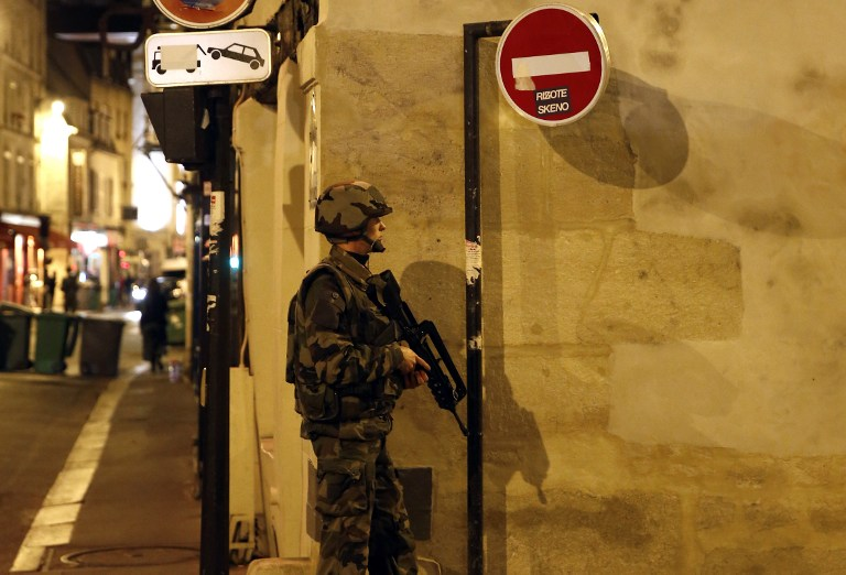 Soldiers secure the area near La Belle Equipe, rue de Charonne, at the site of an attack on Paris on November 14, 2015 after a series of gun attacks occurred across Paris as well as explosions outside the national stadium where France was hosting Germany. More than 100 people were killed in a mass hostage-taking at a Paris concert hall and many more were feared dead in a series of bombings and shootings, as France declared a national state of emergency. Photo: AFP/Pierre Constant.