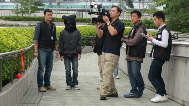 One of the suspects was brought to the LegCo demonstration area for a reenactment.