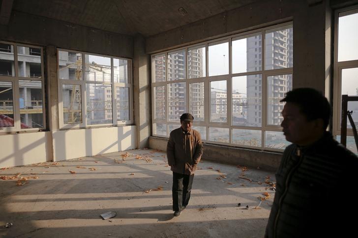 Migrant workers walk inside an unfinished building at the construction site of Zixia Garden development complex. Photo: Damir Sagolj, Reuters.
