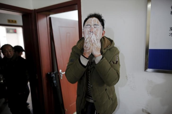 A migrant worker washes his face after waking up. Photo: Damir Sagolj, Reuters.