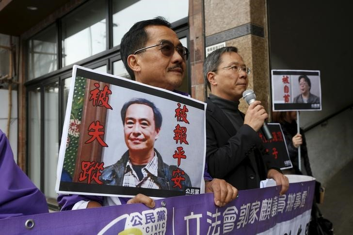 Members from the pro-democracy Civic Party carry a portrait of Lee Bo (L) and Gui Minhai before they protest outside Chinese Liaison Office in Hong Kong, China January 19, 2016. Photo: Reuters/Bobby Yip.