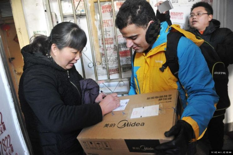 Woman receives package from foreign delivery worker