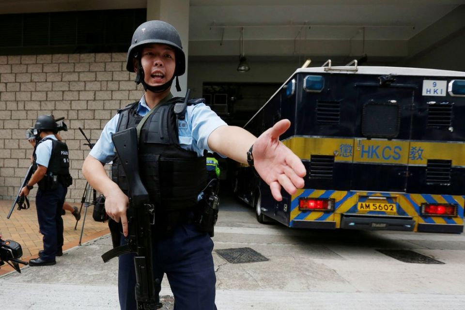 Armed policemen guard the entrance as a prison car carrying British former banker Rurik Jutting enters High Court in Hong Kong