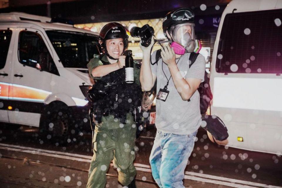 riot police pepper spray reporter