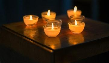 Kerzenschein. Viele kleine Kerzen stehen am Tisch. Ein Ritual.