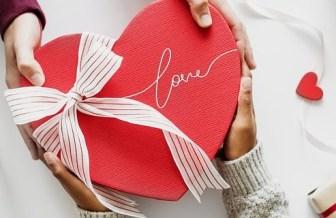 Ein Paket in Herzform wird zwischen zwei Menschen übergeben und ist von vielen Geschenkideen