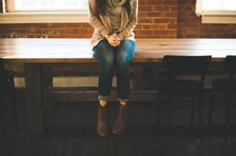 Frau sitzt ohne Selbstbewusstsein mit gefalteten Hände auf dem Tisch