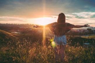Eine Frau sagt Mantras beim Sonnenuntergang