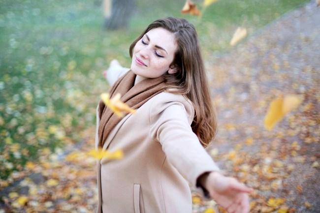 Eine Frau tanzt unter Herbstblättern, weil sie ein erfülltes Leben führt