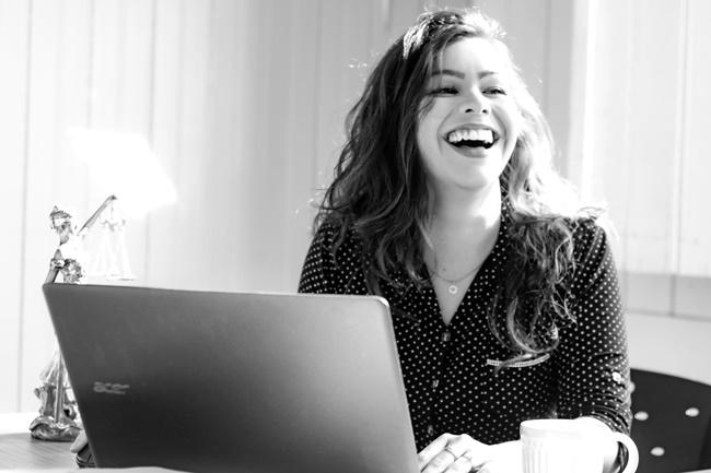 Eine Frau sitzt vor dem PC lacht und macht Selbstmarketing