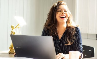 Frau sitzt vor dem PC und informiert sich über Selbstmarketing