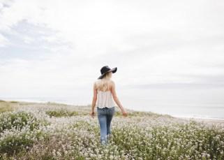 Eine frau geht frei über Wiesen, sie hat sich von emotionaler Abhängigkeit gelöst