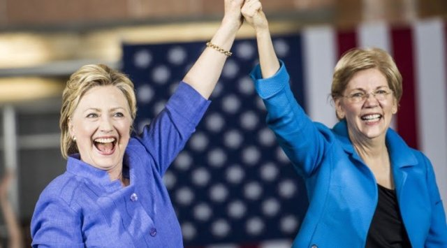 Elizabeth Warren clasping hands with Hillary Clinton.