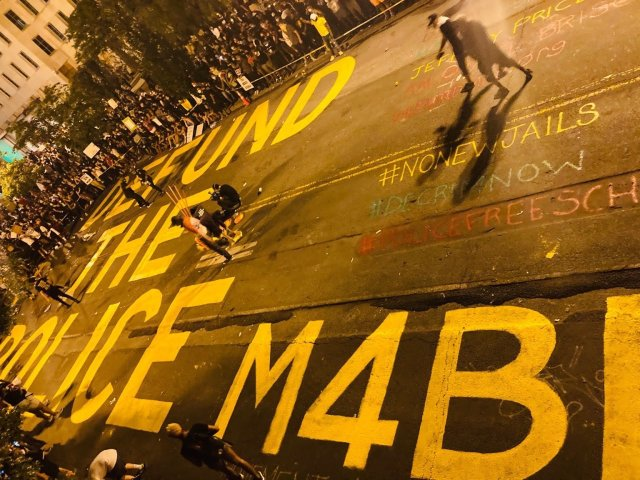 "A picture of a street painted with the message ""Defund the police."""
