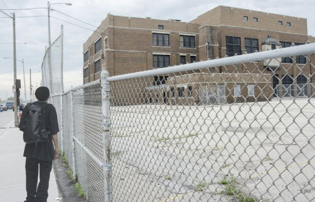An urban school behind a chain link fence. A child looks at it from the sidewalk.