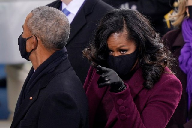 Michelle Obama stands next to Barack Obama and points at the inauguration
