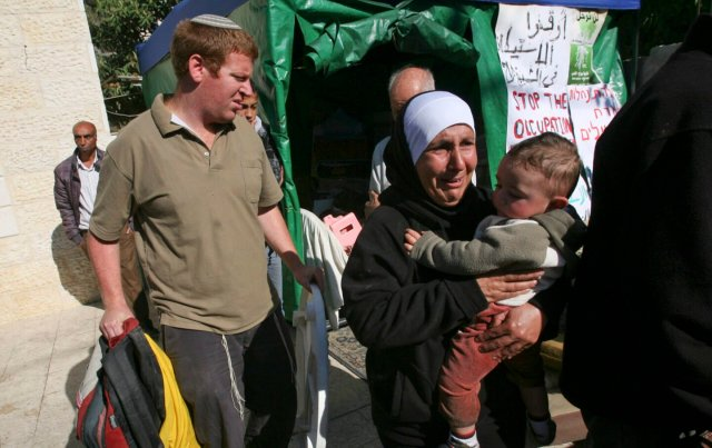 A Palestinian woman reacts as she carries a toddler, while Jewish settlers move out the belongings of a Palestinian family from a house in the east Jerusalem neighborhood of Sheikh Jarrah, Tuesday, Dec. 1, 2009. In an unrest Tuesday, a Jewish family took over a house in an Arab neighborhood of east Jerusalem, sparking a protest by rock-throwing Palestinians and a few Israeli and foreign activists who joined them, police said. One of the family members was lightly injured in the head when a protester hit him with a metal bar, and police arrested five people. Both sides claim ownership of the building. (AP Photo/Dan Balilty)