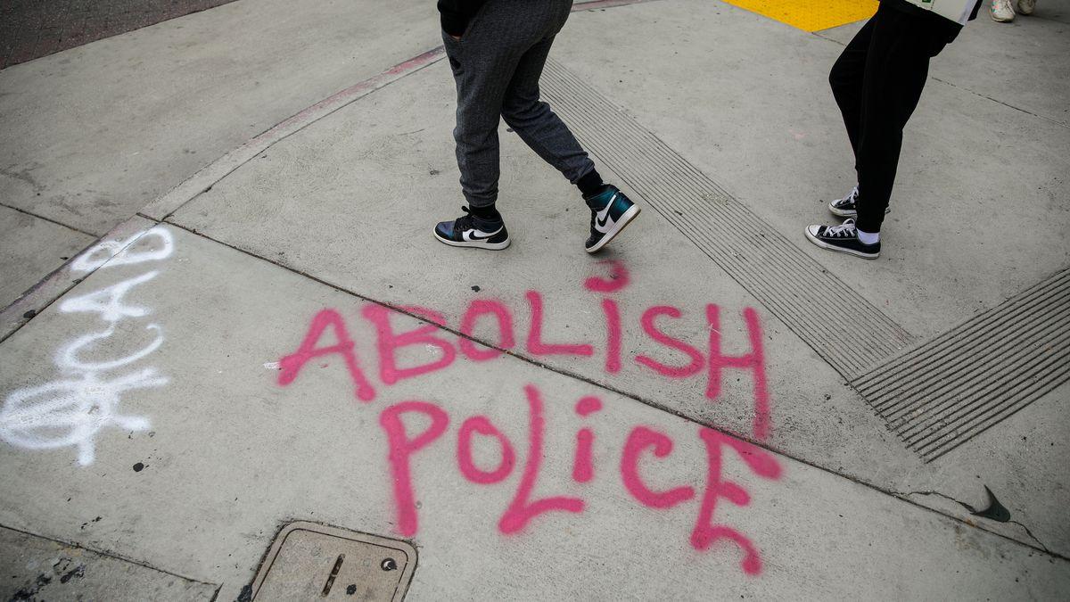 """Graffiti on a sidewalk says """"abolish the police"""""""