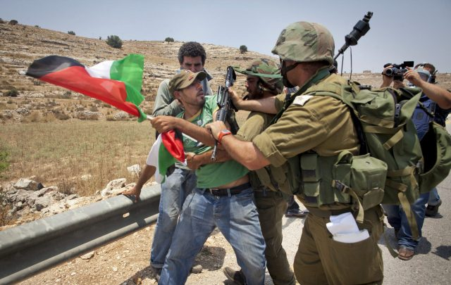 An unidentified protester holding a Palestinian flag scuffles with Israeli security forces during a joint pro-Palestinian demonstration held by foreign, Israeli and Palestinian demonstrators in the West Bank village of Nabi Saleh, Saturday, July 9, 2011. Some of the international pro-Palestinian activists questioned at Israel's airport over the weekend have reached the West Bank and participated in anti-Israel protests Saturday. (AP Photo/Oren Ziv)