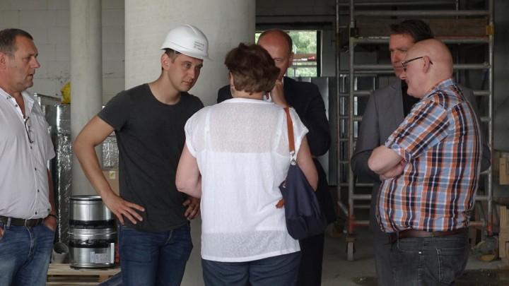 Stijn Langebeek (met bouwhelm), toekomstig hotelmanager, in gesprek met bestuursleden VWH