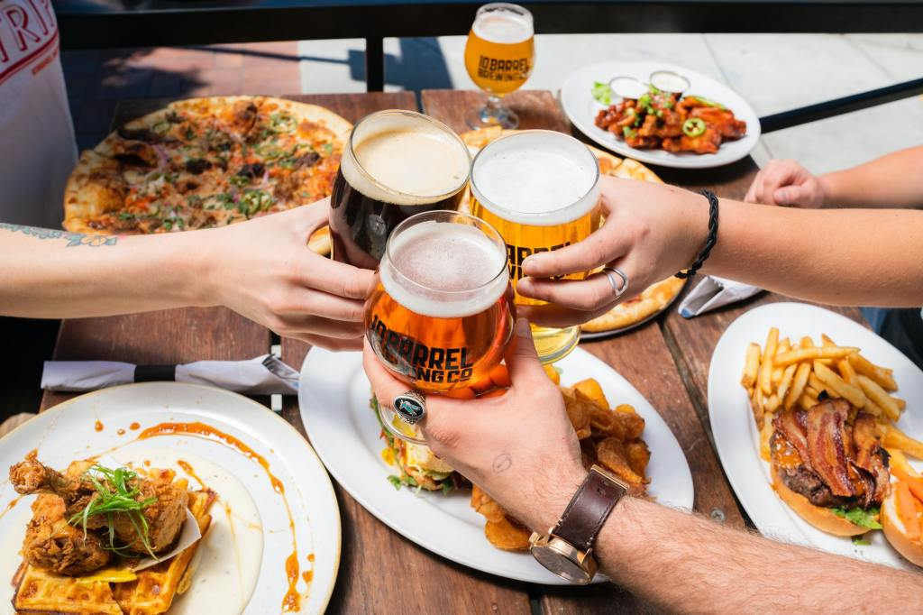 Three friends enjoying different types of beer with food