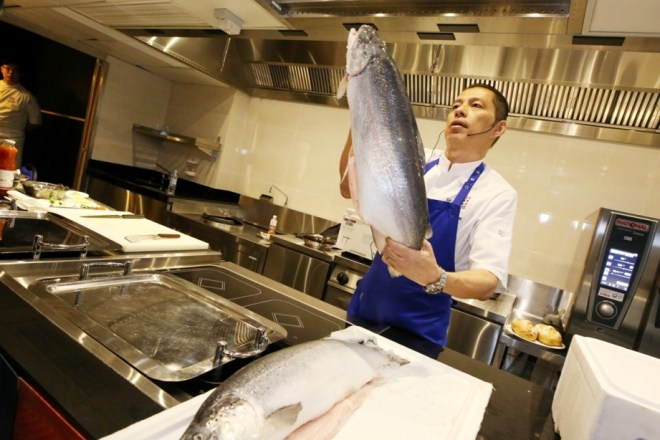 Chef Jimmy Chok holds up the Norwegian Fjord Trout