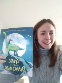 Woman in her early 30s, wearing a grey jumper and holding a copy of the picture book The Girl and the Dinosaur by Hollie Hughes