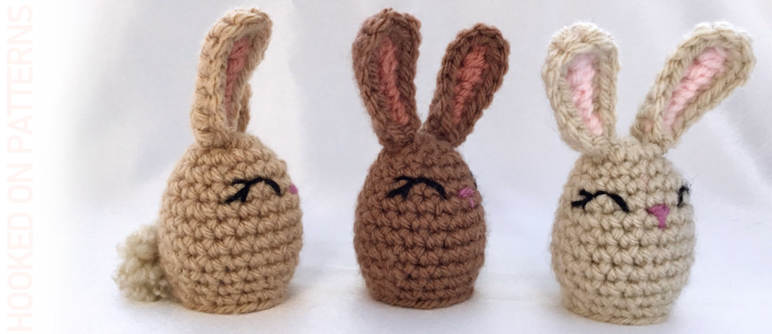 A close up photo of 3 crocheted Easter egg shaped bunnies