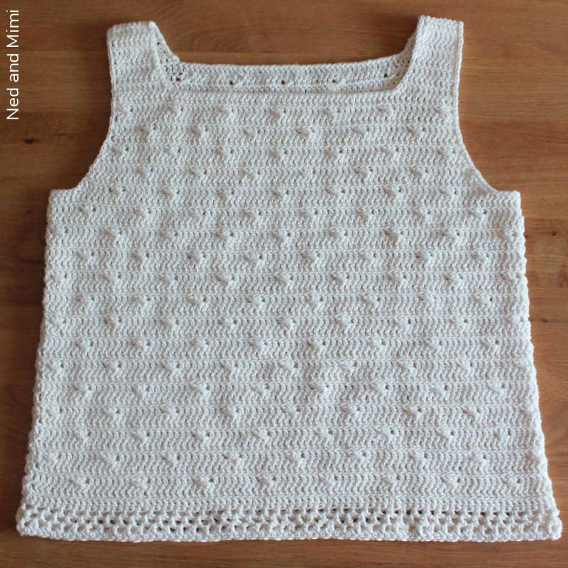 A photo of a delicately textured crochet top laying on a wooden table