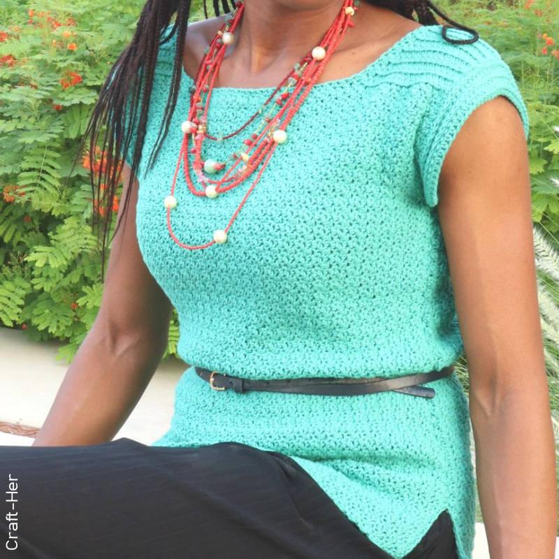A model wearing an aqua coloured, texture rich, crochet top accessorised with a slim black belt.