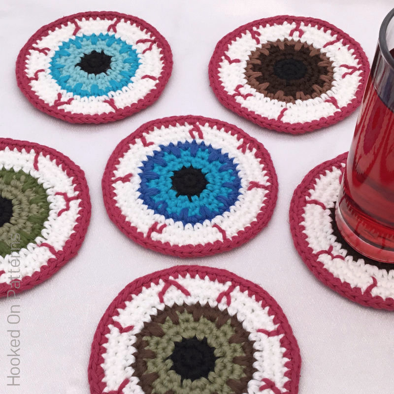 A photo of some eyeball shaped crochet coasters in various colours