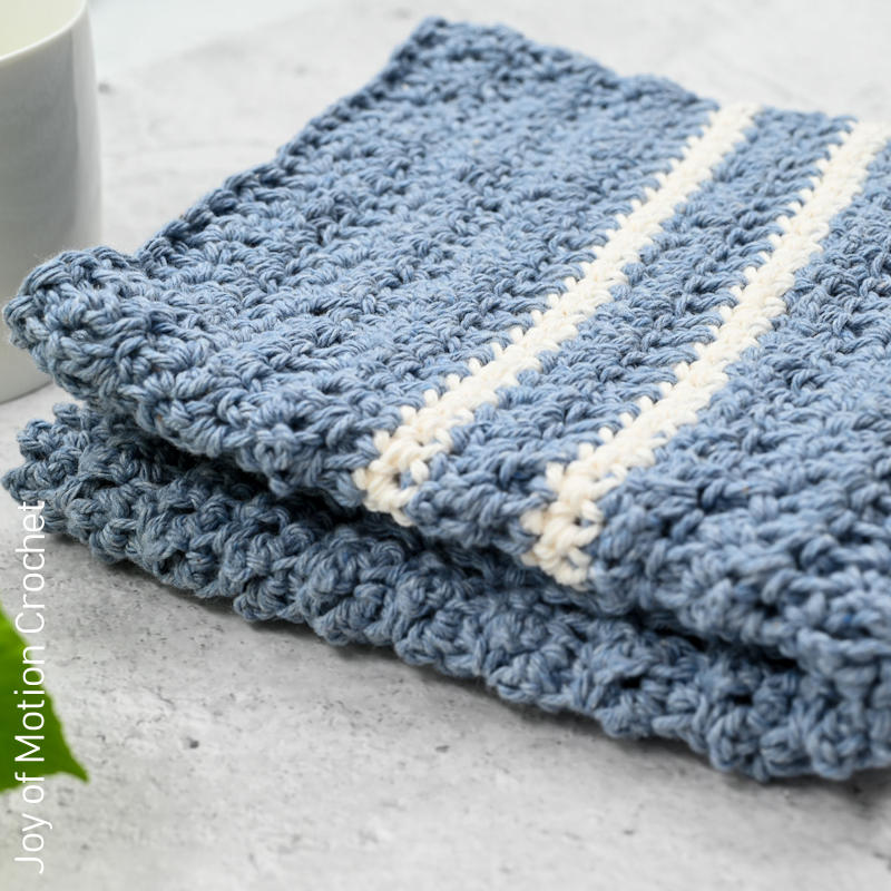 A close up photo of a blue crocheted towel with 2 white stripes.