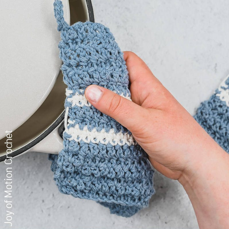 A photo of a hand using a blue potholder with white stripes over a pot handle