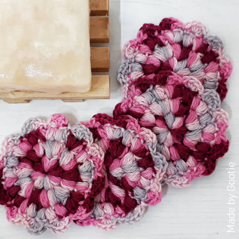 A photo of a set of 4 crocheted face scrubbies in tones of pink with a flowery trim.