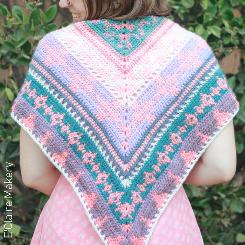 A photo of a crocheted colorwork shawl in tones of pink, purple, white, and teal.