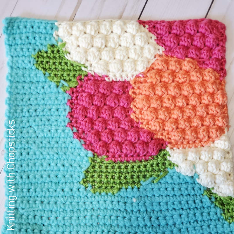 A photo of a colourful crocheted square depicting hydrangea flowers.
