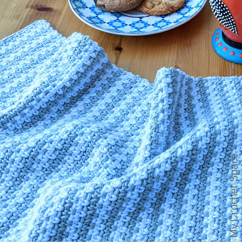 A close up photo of a crocheted moss stitch kitchen tea towel on a wooden kitchen table.