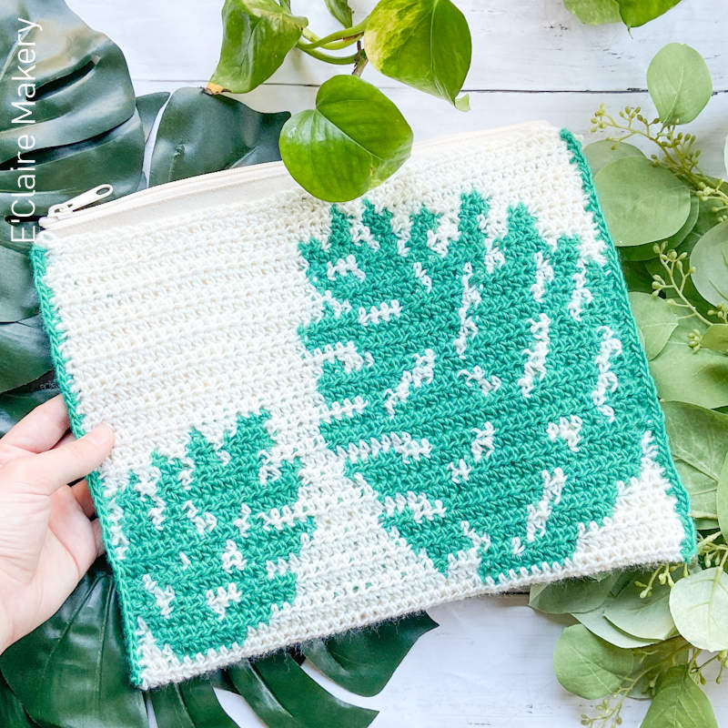 A photo of a crochet pouch with a Monstera leaf design worked in green and white