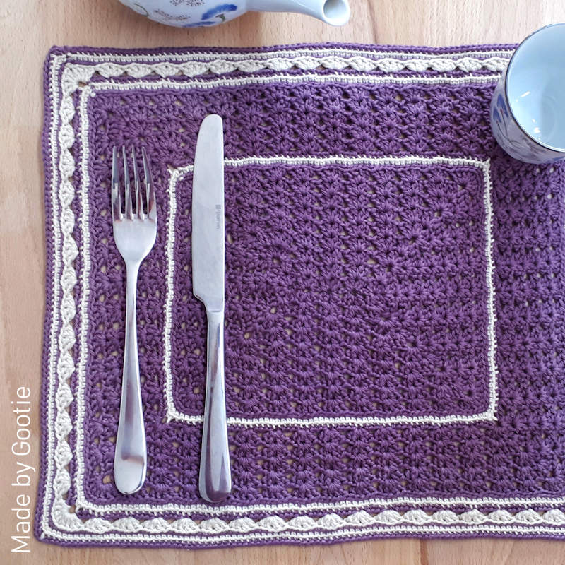 A photo of a purple and white crochet placemat with a lacy effect design