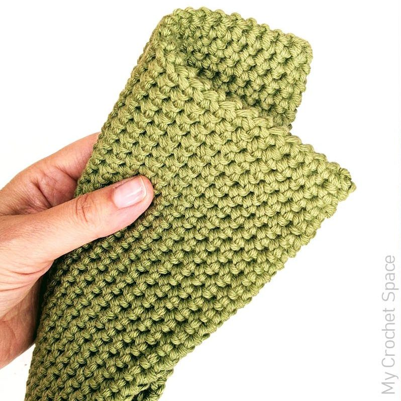 A close up photo of a hand pinching a thick, green, crocheted potholder