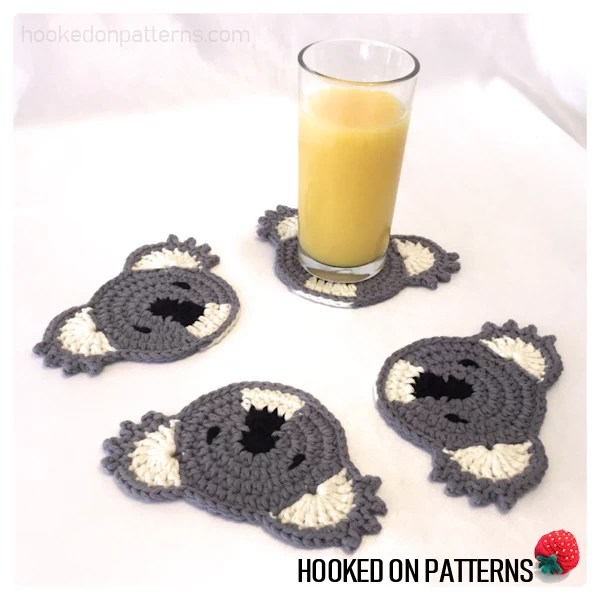 An image showing 4 koala shaped crocheted coasters displayed with a glass of orange juice
