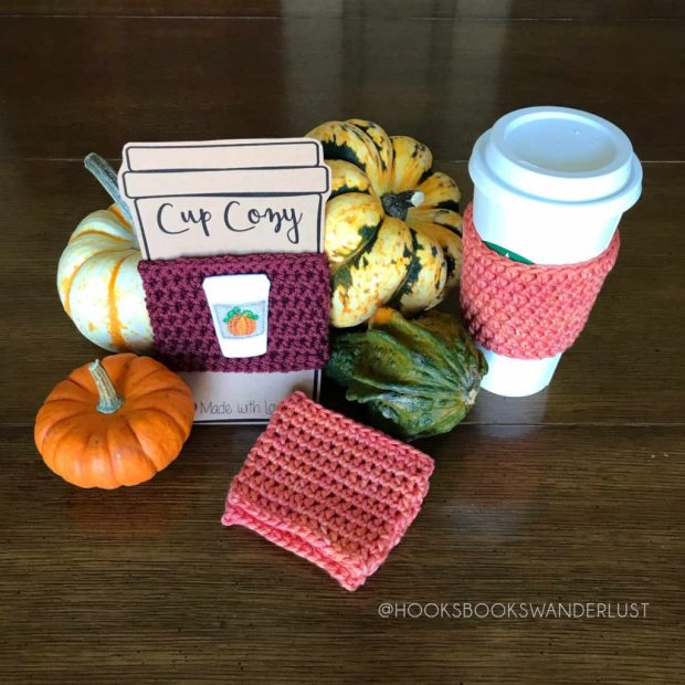 A maroon cup cozy with an embroidered felt pumpkin spiced latte design on it with a kraft card stock insert, an orange un-embellished cup cozy on a venti latte starbucks to go cup, and a stack of two un-embellished orange cup cozies on a dark brown background with miniature gourds surrounding them.