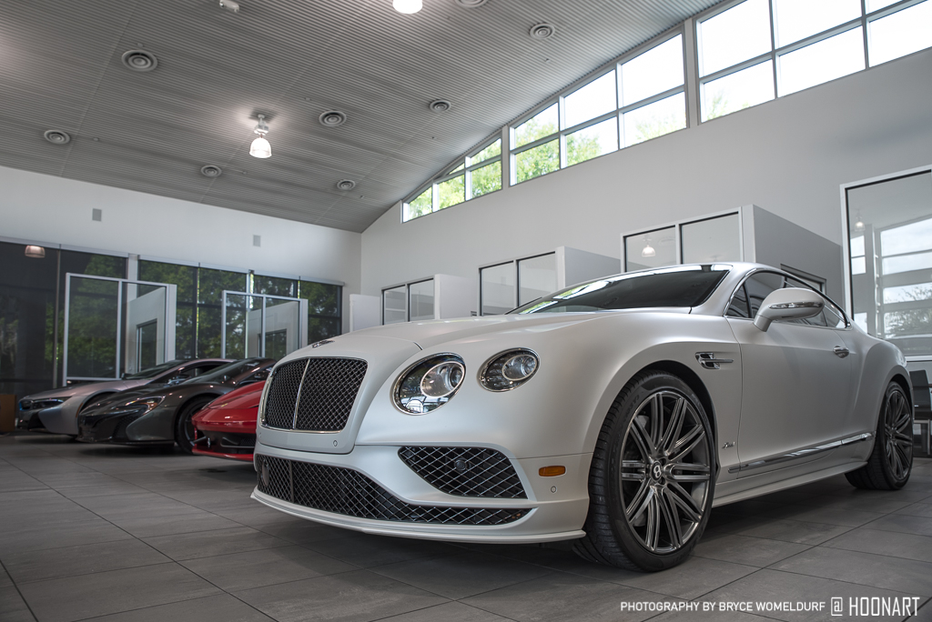 Matte white Bentley Continental GT Speed parked in the showroom of the dealership.