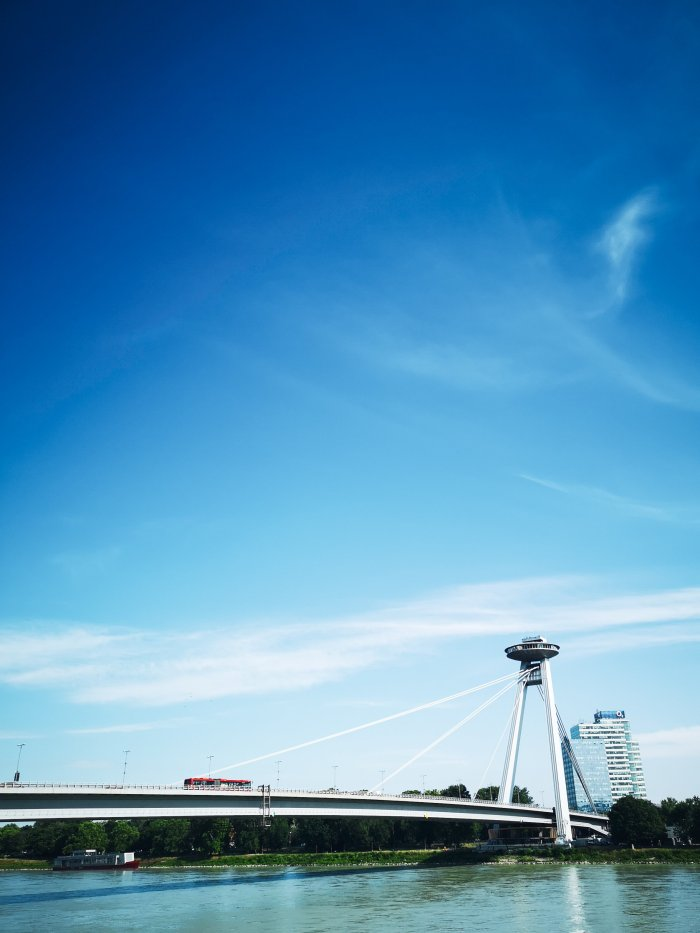 A silver bridge with a UFO structure on top and blue skies - One and Two Day Itineraries To Bratislava + First Timer's Guide: Written By Locals!
