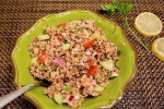 quinoa salad with cumin and lemon served in green bowl with brown placemat