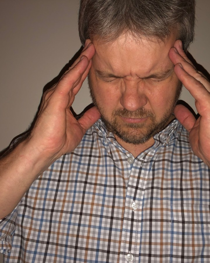 man holding his head with a headache