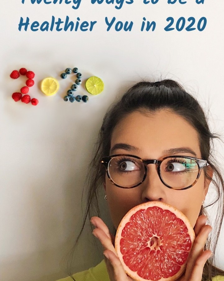 young dark haired woman in glasses doing a wow face with a grapefruit over her mouth